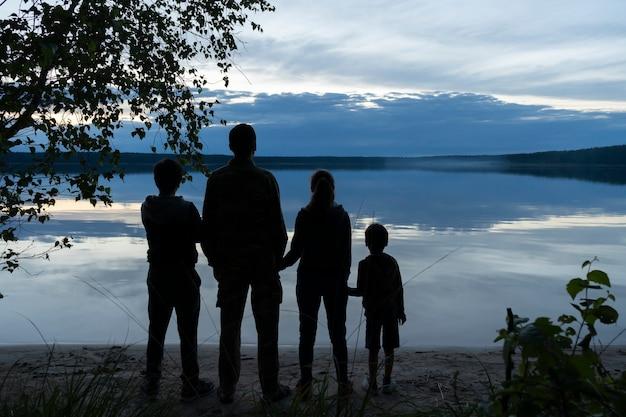 Eine familie - mama, papa und zwei kinder in einer romantischen umgebung am ufer, halten sich an den händen und bewundern das spiegelbild der abendwolken auf der wasseroberfläche