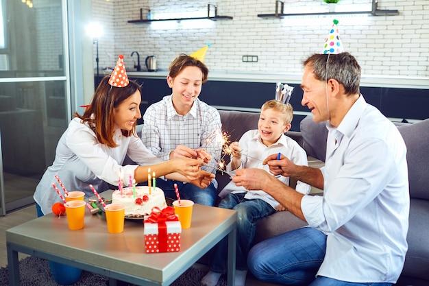 Eine familie mit einem kerzenkuchen feiert eine geburtstagsfeier in einem raum.