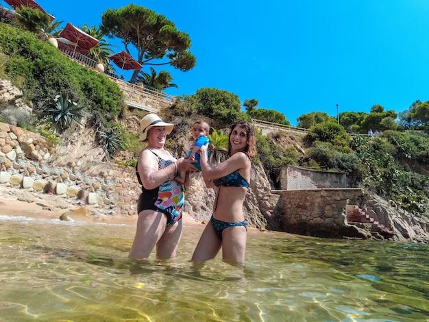 Eine familie mit ihrem baby genießt den sommer in cala canyet neben der stadt tossa de mar. girona, costa brava im mittelmeer
