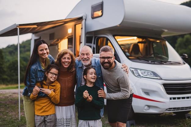Eine familie mit mehreren generationen, die in der abenddämmerung die kamera im freien betrachtet, wohnwagen-urlaubsreise.