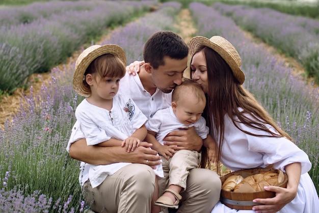 Eine familie mit zwei wunderbaren kindern geht auf einem lavendelfeld spazieren.