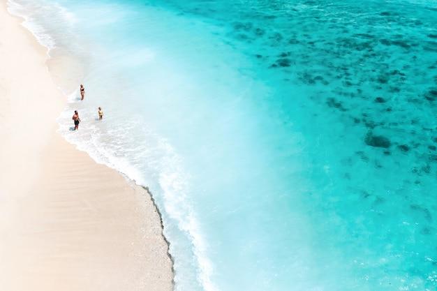 Eine familie steht am strand von le morne im indischen ozean auf der insel mauritius.