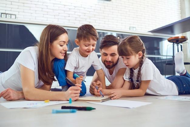 Eine familie zeichnet auf papier, das in ihrer freizeit auf dem boden im zimmer liegt.