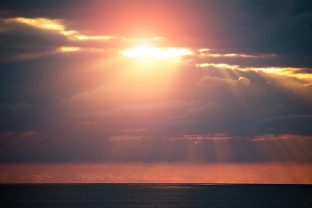 Eine faszinierende seelandschaft mit dramatischen wolken und sonnenlicht zwischen ihnen