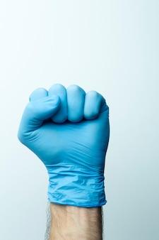 Eine faust in einem medizinischen handschuh. doktorhand in einem blauen medizinischen handschuh auf einem hellen hintergrund.