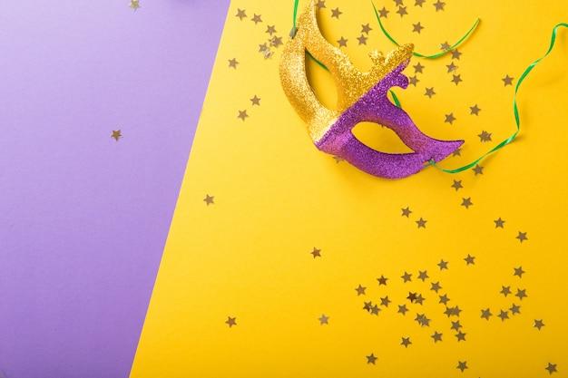 Eine festliche, bunte gruppe von karneval oder karnevalsmaske auf einem gelben lila hintergrund. venezianische masken.