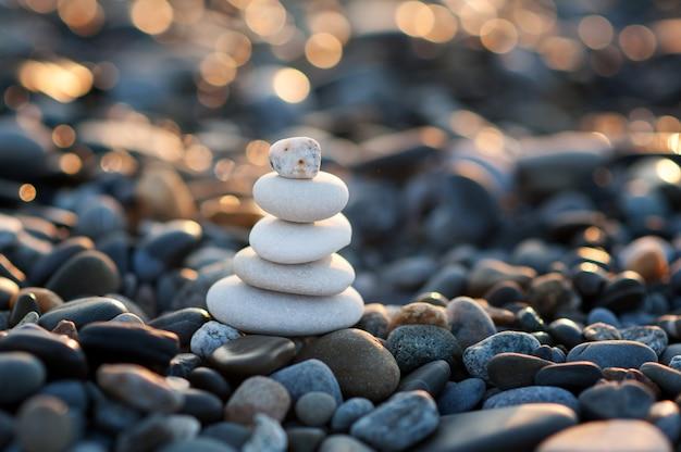 Eine figur aus weißen steinen an der küste in den strahlen der untergehenden sonne zen