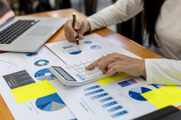 Eine finanzangestellte drückt einen taschenrechner, um die richtigkeit der informationen in den finanzunterlagen des unternehmens zu überprüfen, sie bereitet die finanzübersicht des unternehmens für ein treffen mit der geschäftsführung vor.