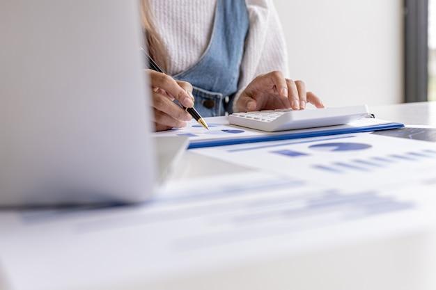 Eine finanzwissenschaftlerin zeigt mit einem stift auf ein dokument, sie analysiert und überprüft die finanzdaten des unternehmens auf richtigkeit, bevor sie sie dem meeting präsentiert. konzept der finanzprüfung.