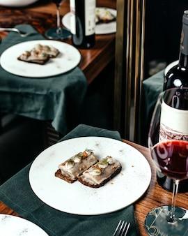 Eine fischmahlzeit der draufsicht innerhalb des weißen tellers zusammen mit rotwein auf dem tischnahrungsmittel-restaurant