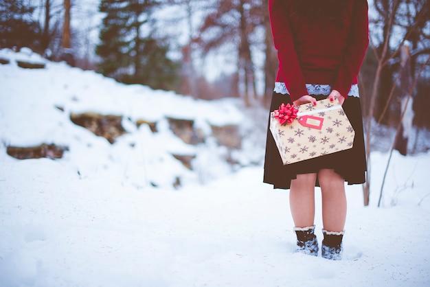 Eine flache fokusaufnahme einer frau, die ein weihnachtsgeschenk hinter ihrem rücken hält