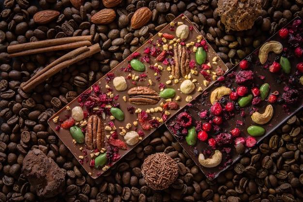 Eine flache komposition aus wunderschönen handgemachten dunklen schokoriegeln, die nüsse und beeren sowie pralinen enthalten