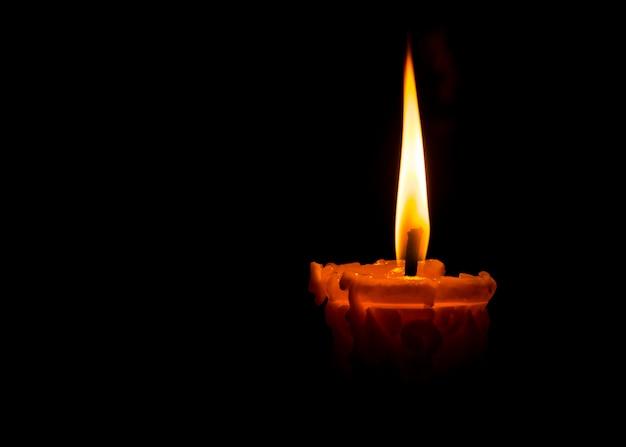 Eine flamme von einer kerze am dunklen nachthintergrund