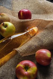 Eine flasche apfelessig nahaufnahme. apfelwein und äpfel auf sackleinen.