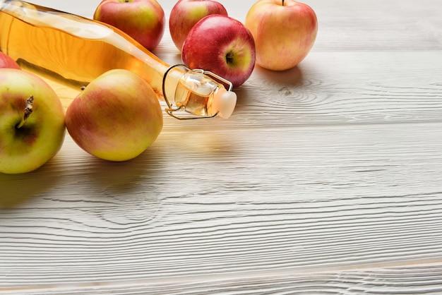 Eine flasche apfelsaft und äpfel auf einem weißen holztisch mit kopienraum. eine flasche apfelessig nahaufnahme.