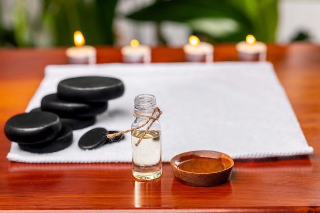 Eine flasche aromaöl vor einem frottiertuch, auf dem steine für therapiesteine und kerzen liegen
