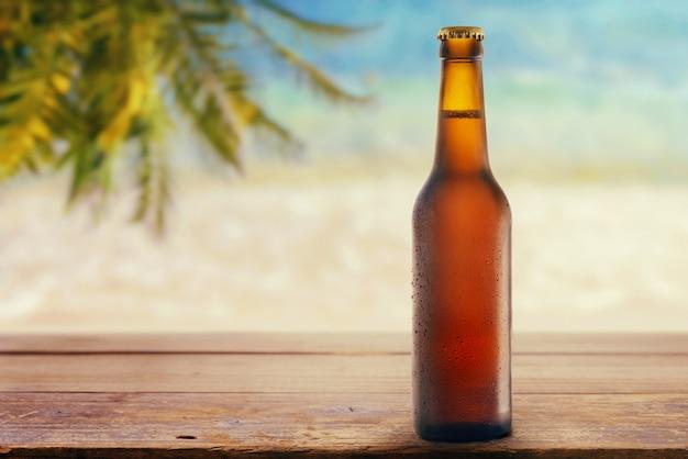 Eine flasche bier am meeresstrand
