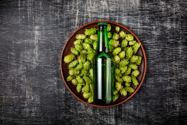 Eine flasche bier auf einem grünen frischen hopfen in einer platte vor dem hintergrund einer schwarzen verkratzten tafel