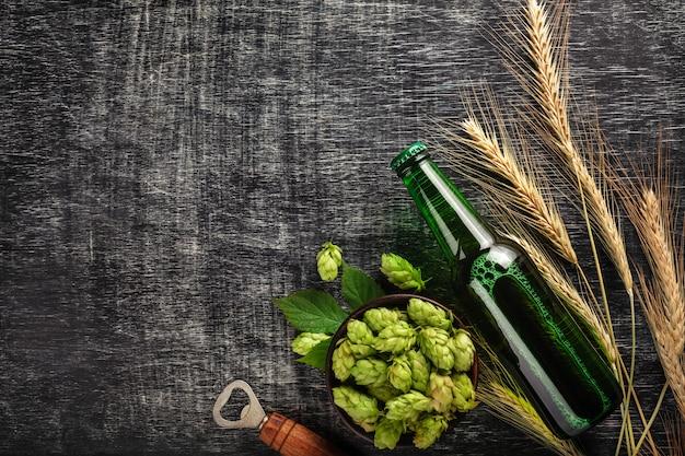 Eine flasche bier mit grünen hopfen, ährchen und öffner auf einem schwarzen zerkratzten kreidebrett