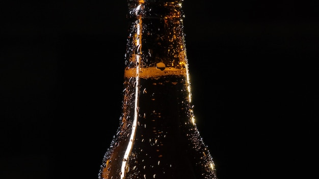 Eine flasche bier wird von einer männlichen hand geöffnet. flasche bier mit wassertropfen auf einer schwarzen wandnahaufnahme. zeitlupe.