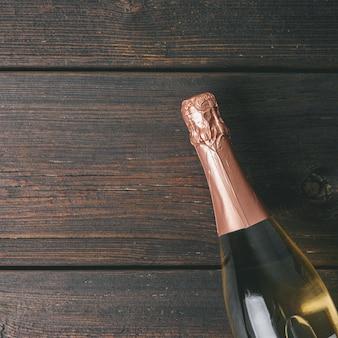 Eine flasche champagner auf hölzernem hintergrund