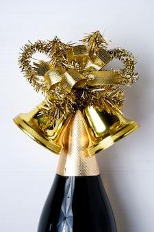 Eine flasche champagner mit weihnachtsglocken verziert