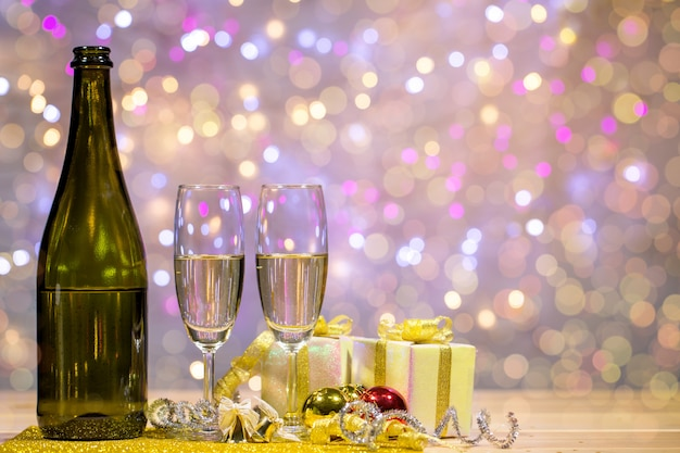 Eine flasche champagner und gläser werden zusammen mit einer geschenkbox und glänzenden kugeln platziert. platz oben rechts für ihre formulierung.