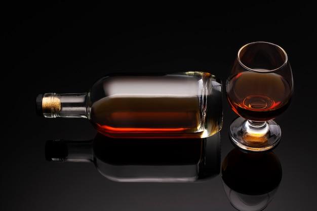 Eine flasche cognac und ein glas auf dunklem hintergrund