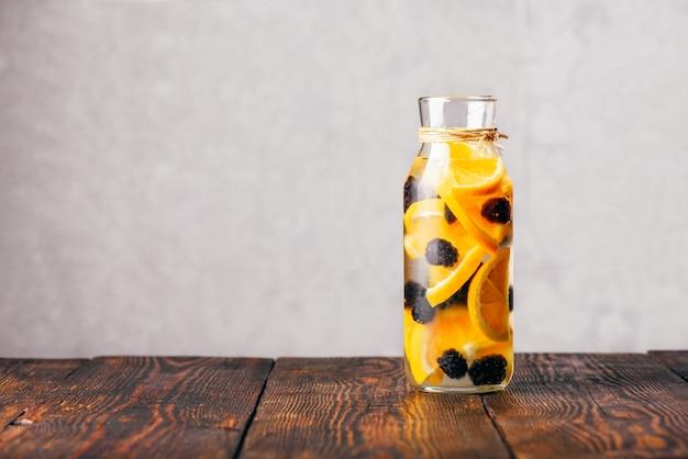 Eine flasche detox-wasser mit geschnittener roher orange und frischer brombeere.