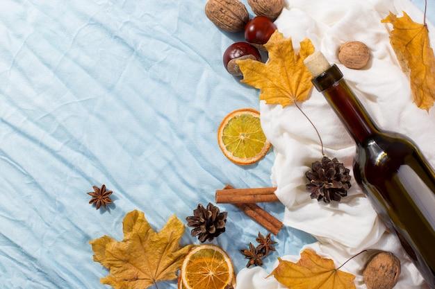 Eine flasche glühwein mit gewürzen, schal, trockenen blättern und orangen auf einem tisch. herbststimmung, eine methode, um in der kälte warm zu halten, copyspace.