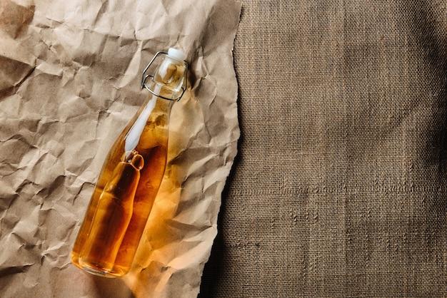 Eine flasche hausgemachten cidre liegt auf kraftpapier und sackleinen mit kopierraum.