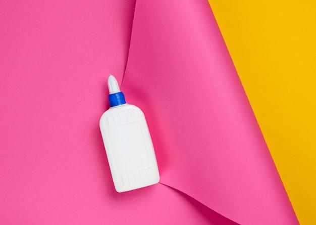 Eine flasche kleber auf einem farbigen studiopapier