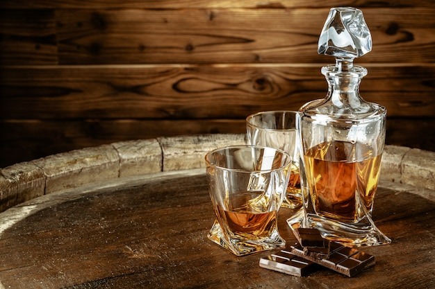 Eine flasche kognak und glas auf braunem holz. brandy