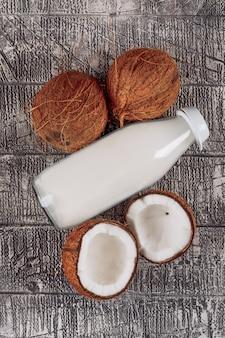 Eine flasche milch mit in zwei hälften geteilten kokosnüssen auf grauem holzhintergrund, flach gelegen.