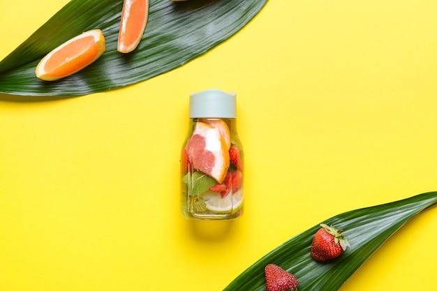 Eine flasche minzwasser mit zitrusfrüchten und beeren im farbraum