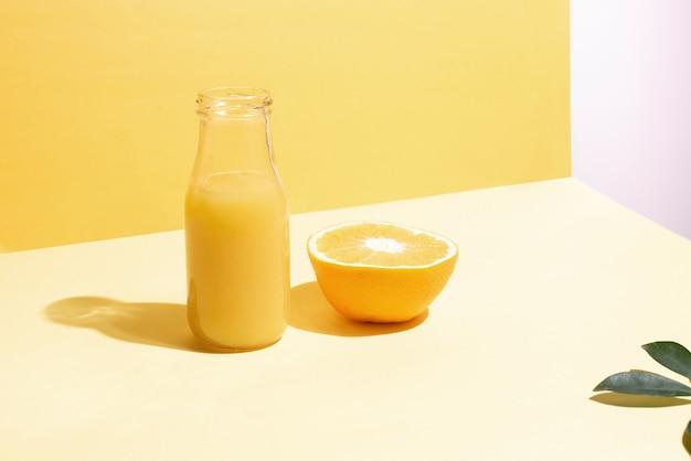 Eine flasche mit orangensaft und eine halbe orange in den sonnenstrahlen