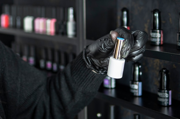 Eine flasche nagellack in der hand einer frau. wählen sie die farbe des nagellacks. die maniküre öffnet eine flasche nagellack.. set mit verschiedenen nagellacken in den regalen im kosmetikgeschäft