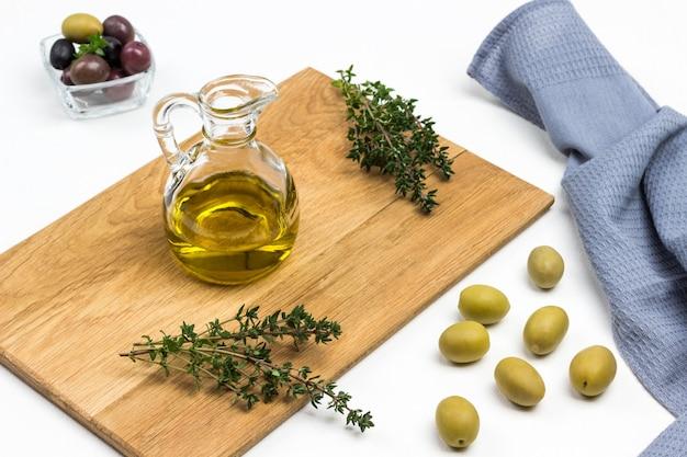 Eine flasche olivenöl und thymianzweige an bord. oliven und graue serviette auf dem tisch. draufsicht.