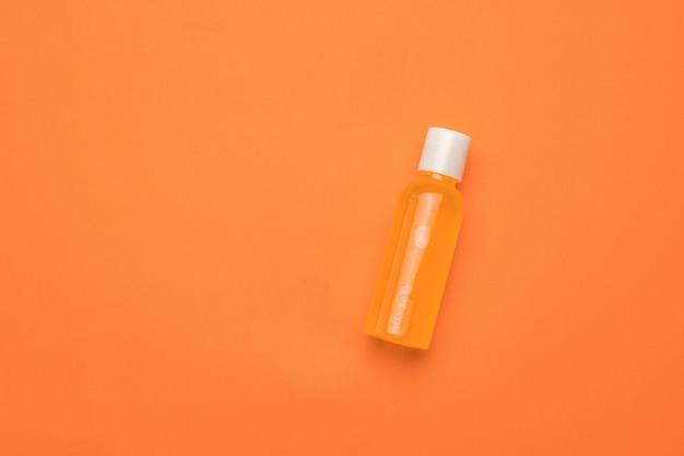 Eine flasche orangensaft auf orangefarbenem hintergrund. minimalismus.