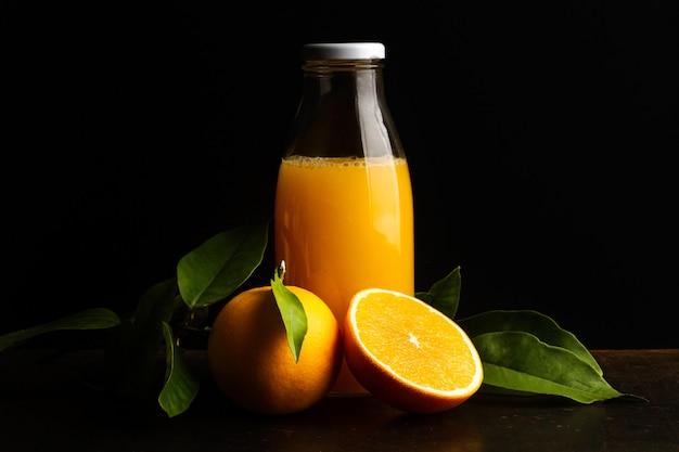 Eine flasche orangensaft und eine halbierte orange auf dunklem hintergrund
