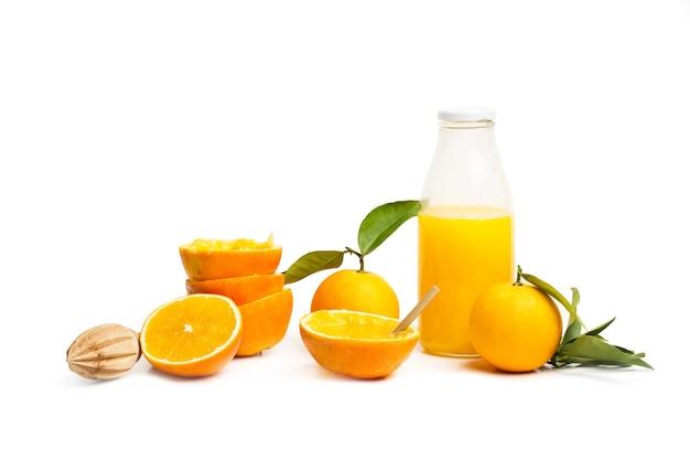 Eine flasche orangensaft und halbierte orangen auf weißem hintergrund