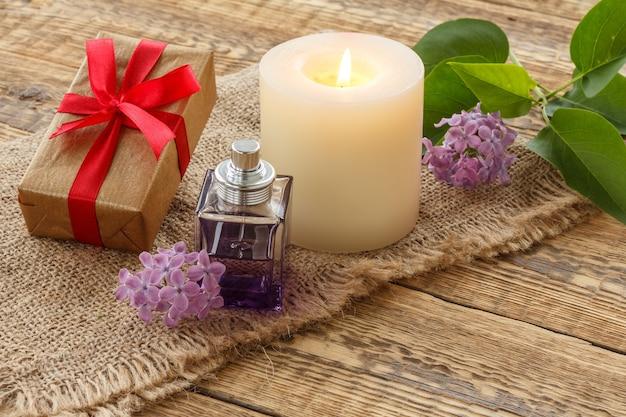 Eine flasche parfüm, eine brennende kerze, eine geschenkbox und lila blumen auf sackleinen und alten holzbrettern.