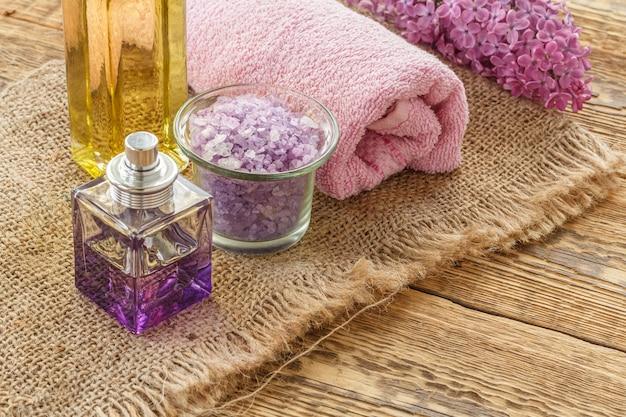 Eine flasche parfüm, eine glasschüssel mit meersalz, eine flasche öl, lila blumen und ein handtuch für badezimmerverfahren auf sackleinen und holzbrettern. spa-produkte und zubehör. ansicht von oben.