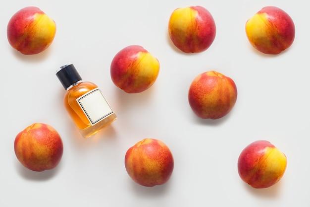 Eine flasche pfirsichöl, verziert mit einem pfirsichmuster an einer weißen wand. das konzept eines aromaöls, die inhaltsstoffe eines aromaöls oder die aromatherapie.