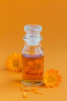 Eine flasche ringelblumentinktur oder aufguss mit frischen ringelblumenblüten auf einer orange. natürliche pflanzliche alternativmedizin, heil- und heilkräuter.