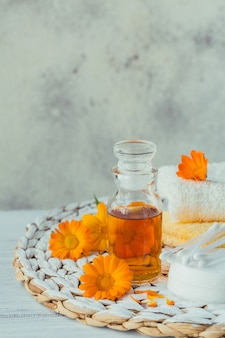 Eine flasche ringelblumentinktur oder aufguss mit frischen ringelblumenblüten und wattepad und klebt auf einem weiß. natürliche pflanzliche alternativmedizin, heil- und heilkräuter.