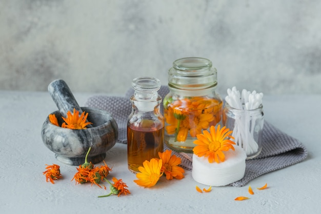 Eine flasche ringelblumentinktur oder aufguss, salbe, creme oder balsam mit frischer und trockener ringelblume, wattepad und weißen stiften