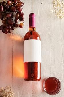 Eine flasche roséwein mit einem leeren etikett und einem glas wein und trauben