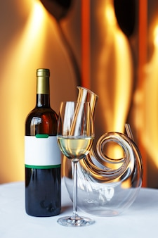 Eine flasche rotwein, ein glas wein und eine karaffe auf einem tisch mit einer weißen tischdecke.