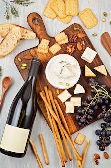 Eine flasche rotwein, käse, brot und cracker für die buffetparty. traditionelles französisch oder italienisch führt zu einer flachen lage. draufsicht